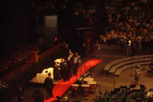 Clear down below, Huh receives her diploma.